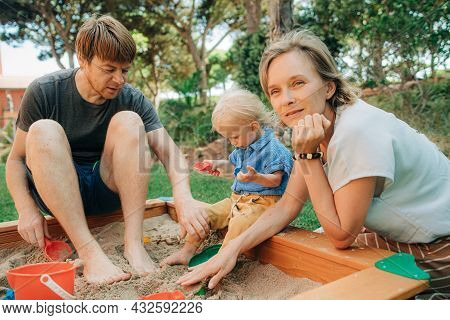 Mid Adult Woman Playing With Child In Sandbox. Father Sitting With Daughter In Sandpit, Woman Lookin