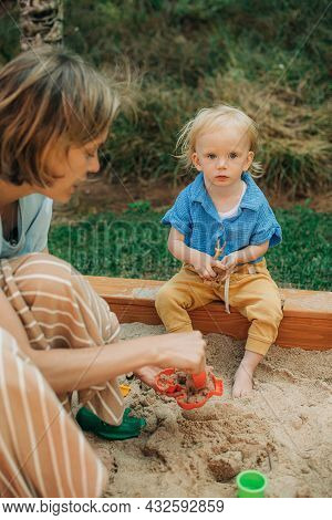 Portrait Of Cute Little Girl Sitting In Sandbox. Mother Playing With Her Daughter Outdoors. Childhoo