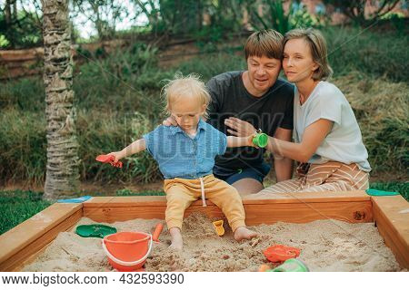 Happy Couple Looking After Little Child In Sandpit. Man And Woman Sitting At Sandbox And Little Girl