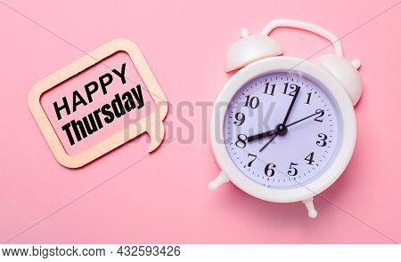 On A Delicate Pink Background, A White Alarm Clock And A Wooden Frame With The Text Happy Thursday