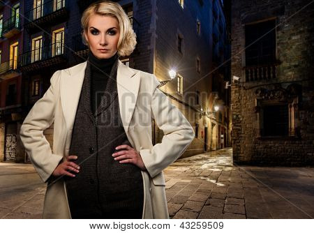 Blond woman in white coat alone outdoors at night