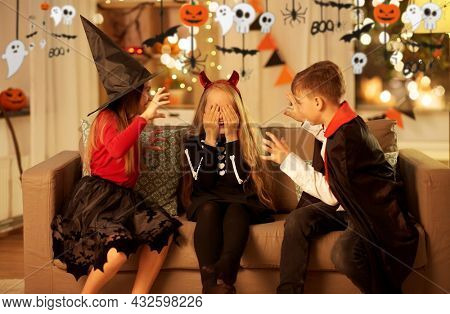halloween, holiday and childhood concept - smiling boy and girls in costumes playing and scaring each other at home at night decorated with garland and lights