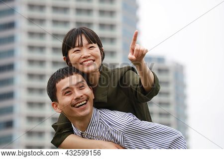 A smiling couple with a piggyback ride