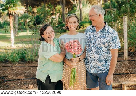 Happy Mature Couple With Adult Daughter. Portrait Of Smiling Mid Adult Woman Holding Flowers Posing