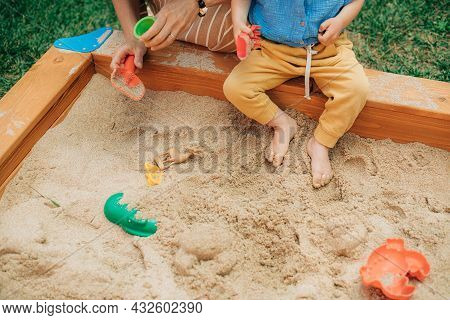 Close-up Of Little Child Sitting In Sandbox With Mother. Toddler Kid Playing In Sandpit With Mom Out
