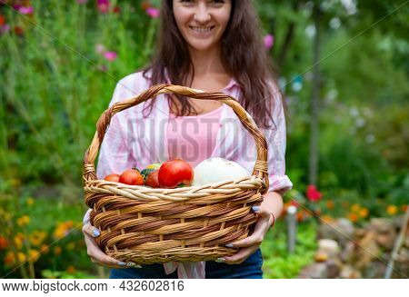 Faceless Happy Smiling Woman Farmer Holding A Basket Of Vegetables From Her Vegetable Garden. Close