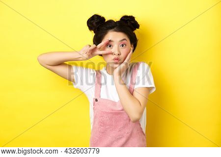 Kawaii Asian Girl Showing V-sign And Pouting Cute, Making Silly Face With Makeup, Standing On Yellow