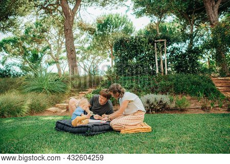 Happy Family Painting Together On Grass Outdoors. Mid Adult Man And Woman Sitting On Mattress And Pl
