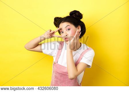 Beautiful Asian Girl Showing V-sign And Pouting Cute, Making Silly Face With Makeup, Standing On Yel