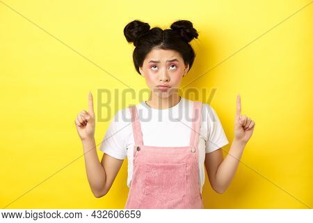 Skeptical Teenage Asian Girl With Glam Pink Makeup, Pointing And Looking Up Unamused, Standing Reluc