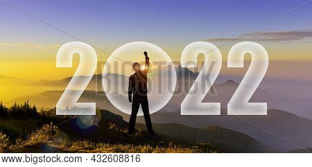 Happy New Year 2022. Silhouette Of Man Hands Up To Challenge 2022 On Mountain Hill. Man Silhouette A