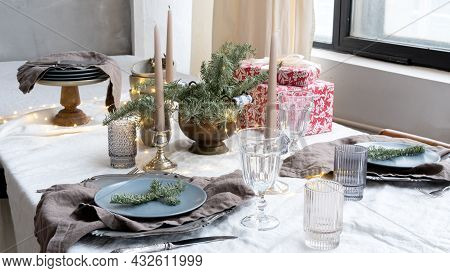 Christmas Table Setting For A Festive Dinner. Dinnerware, Candles And Gift Boxes On The Set Table In