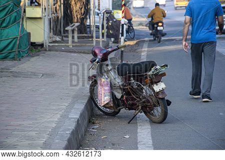 Stock Photo Of Maroon Color M80 Motorbike Parked Near Sidewalk Or Footpath, People Roaming On Road ,
