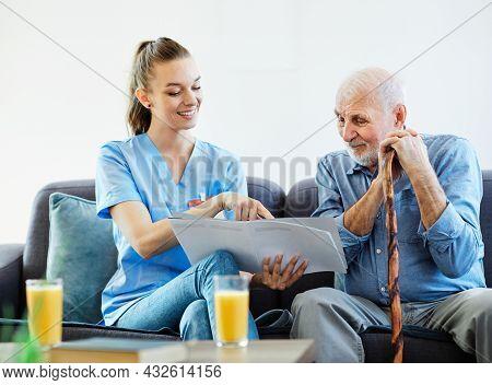 Doctor Or Nurse Caregiver Showing A Brochure To Senior Man At Home Or Nursing Home