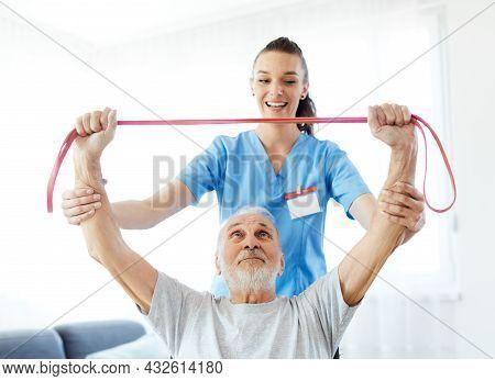 Doctor Or Nurse Caregiver Exercise With Senior Man At Home Or Nursing Home