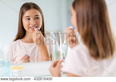 beauty and cosmetics concept - teenage girl applying lip balm and looking to mirror at home bathroom