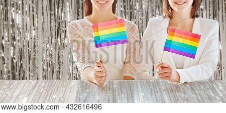 homosexuality, gay pride and lgbt concept - close up of happy lesbian couple holding rainbow flags over foil party curtain on background