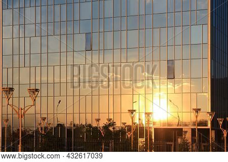 Clouds And Sunset Reflection In Glass Office Building. Sunset And Clouds Reflected In The Glass Faca