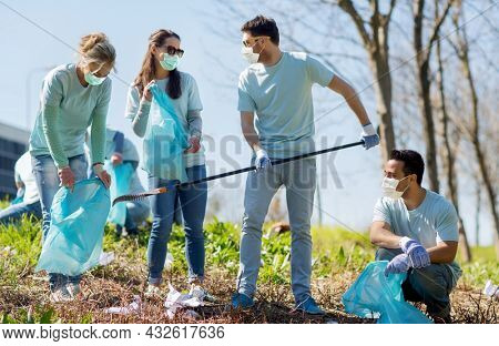 volunteering, health and ecology concept - group of volunteers wearing face protective medical masks for protection from virus disease with garbage bags cleaning area in park