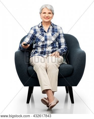 comfort, furniture and old people concept - smiling senior woman with remote control watching tv sitting in modern armchair over white background