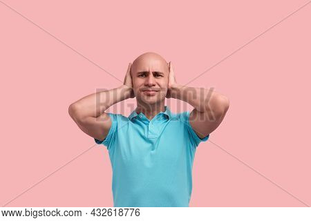 Upset Bald Homosexual Man With Bristle Closes Ears With Hands, Does Not Want To Hear Loud Music, Fro