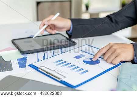 Businessman Is Using Tablet To Compare Information On Financial Documents, He Is Checking Company Fi