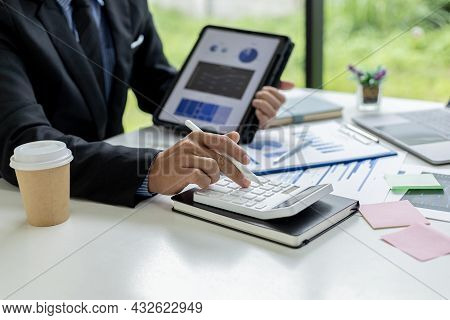 Close-up Of A Business Man Using A White Calculator, A Financial Businessman Examining The Numerical