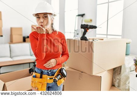 Middle age grey-haired woman wearing hardhat standing at new home looking at the camera blowing a kiss with hand on air being lovely and sexy. love expression.