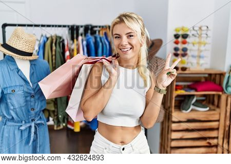 Young caucasian woman holding shopping bags at retail shop smiling with happy face winking at the camera doing victory sign with fingers. number two.