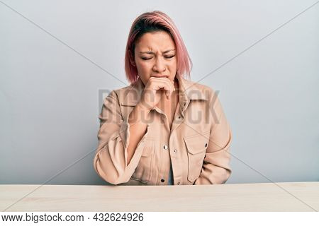 Hispanic woman with pink hair wearing casual clothes sitting on the table feeling unwell and coughing as symptom for cold or bronchitis. health care concept.