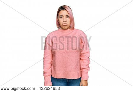 Hispanic woman with pink hair wearing casual winter sweater depressed and worry for distress, crying angry and afraid. sad expression.