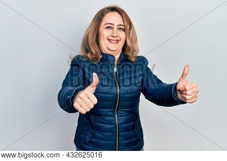 Middle age caucasian woman wearing casual clothes approving doing positive gesture with hand, thumbs up smiling and happy for success. winner gesture.