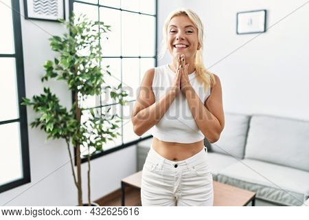 Young caucasian woman standing at living room praying with hands together asking for forgiveness smiling confident.