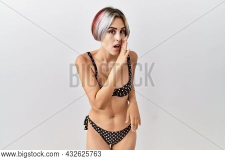 Young beautiful woman wearing swimsuit over isolated background hand on mouth telling secret rumor, whispering malicious talk conversation