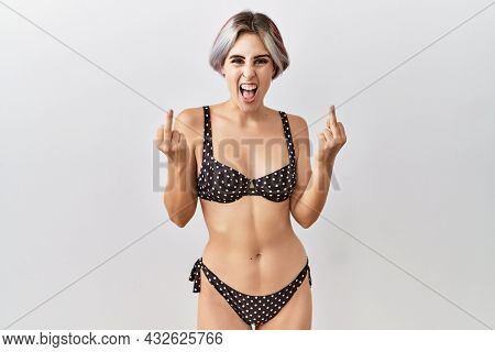 Young beautiful woman wearing swimsuit over isolated background showing middle finger doing  bad expression, provocation and rude attitude. screaming excited
