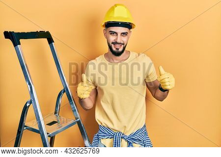 Handsome man with beard by construction stairs wearing hardhat success sign doing positive gesture with hand, thumbs up smiling and happy. cheerful expression and winner gesture.