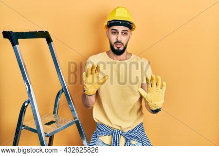 Handsome man with beard by construction stairs wearing hardhat moving away hands palms showing refusal and denial with afraid and disgusting expression. stop and forbidden.