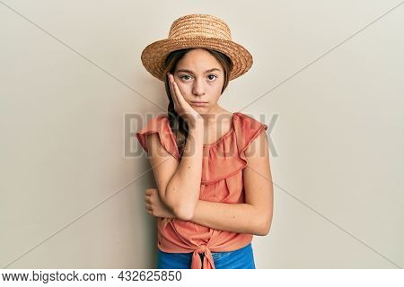 Beautiful brunette little girl wearing summer hat thinking looking tired and bored with depression problems with crossed arms.