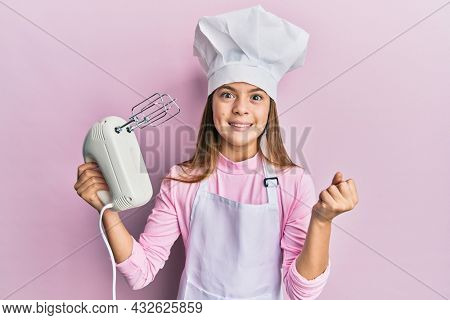 Beautiful brunette little girl wearing chef hat holding pastry blender electric mixer screaming proud, celebrating victory and success very excited with raised arm