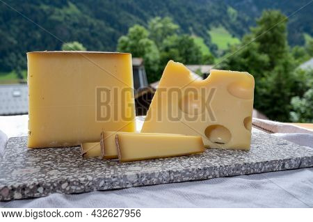 Cheese Collection, Swiss Cow Cheese Emmental And Gruyere And Mountains Village In Apls On Background