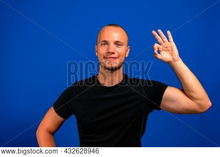 Cheerful Man In Casual T-shirt On Face Smiling On Camera With Alright Sign Isolated Over Blue Backgr