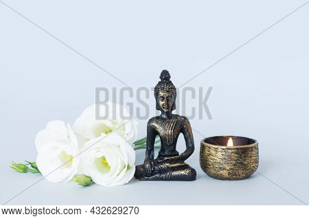 Buddha Statue On Altar With Candle And Flowers. Meditation, Buddhism And Enlightenment Concept