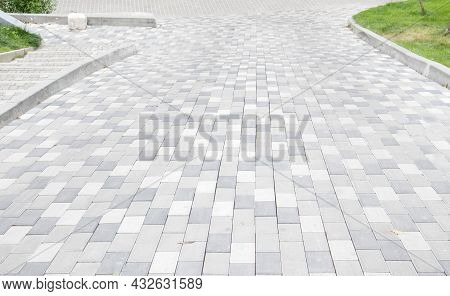 A Long Descent Covered With Gray Paving Slabs. The Ramp Is Paved With Concrete Tiles. Wheelchair And