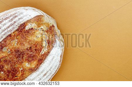 Freshly Baked Organic Sourdough Bread Isolated On Brown Or Coffee Background. One Loaf Of Delicious