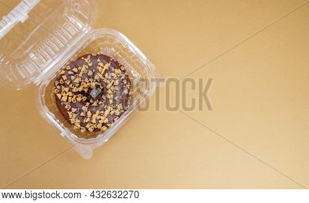Chocolate Donut In A Plastic Container On A Brown Or Coffee Background. Takeaway Breakfast Concept.