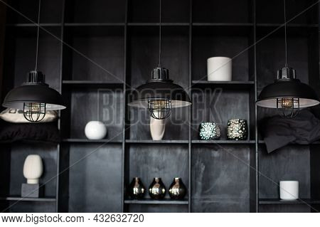 Metal Chandeliers In Retro Style On Background Wooden Shelves With Decor. Dark Room With Three Moder