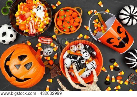 Halloween Trick Or Treat Scene With Jack O Lantern Pails And A Variety Of Candy. Top View On A Black