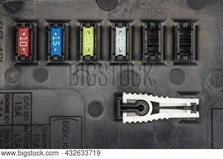 Automotive Fuses On A Black Panel With Holders And Multi-colored Markings - A Protective Device That