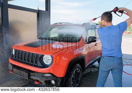 A Man Washing A Car With Foam From A Hose At A Car Wash