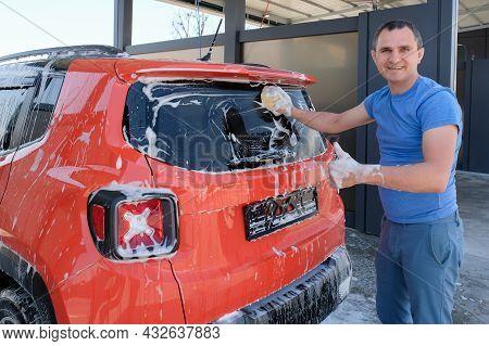 Happy Man Washes A Car At A Car Wash. Car In Foam